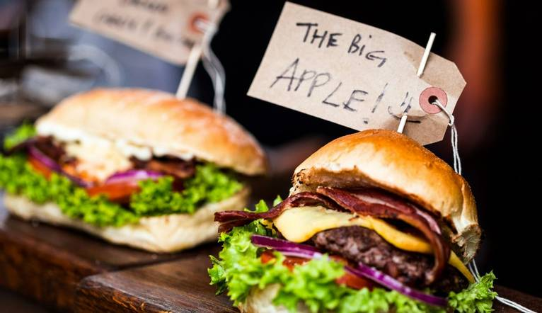 Close up colour image of two freshly flame grilled burgers next to each other on a market stall at Borough Market, a famous …