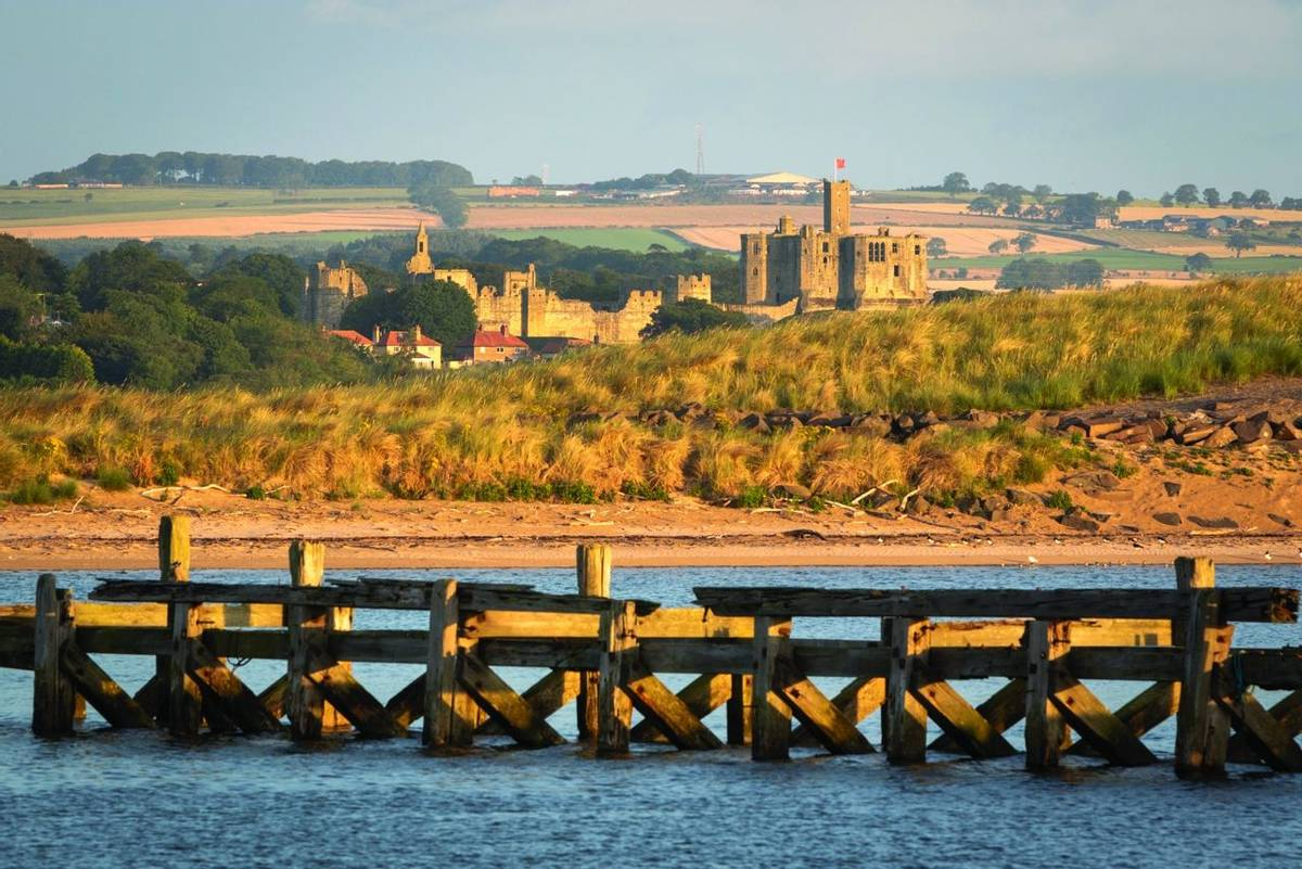 View of Warkworth castle from a distance in the early morning. Northumberland, United Kingdom