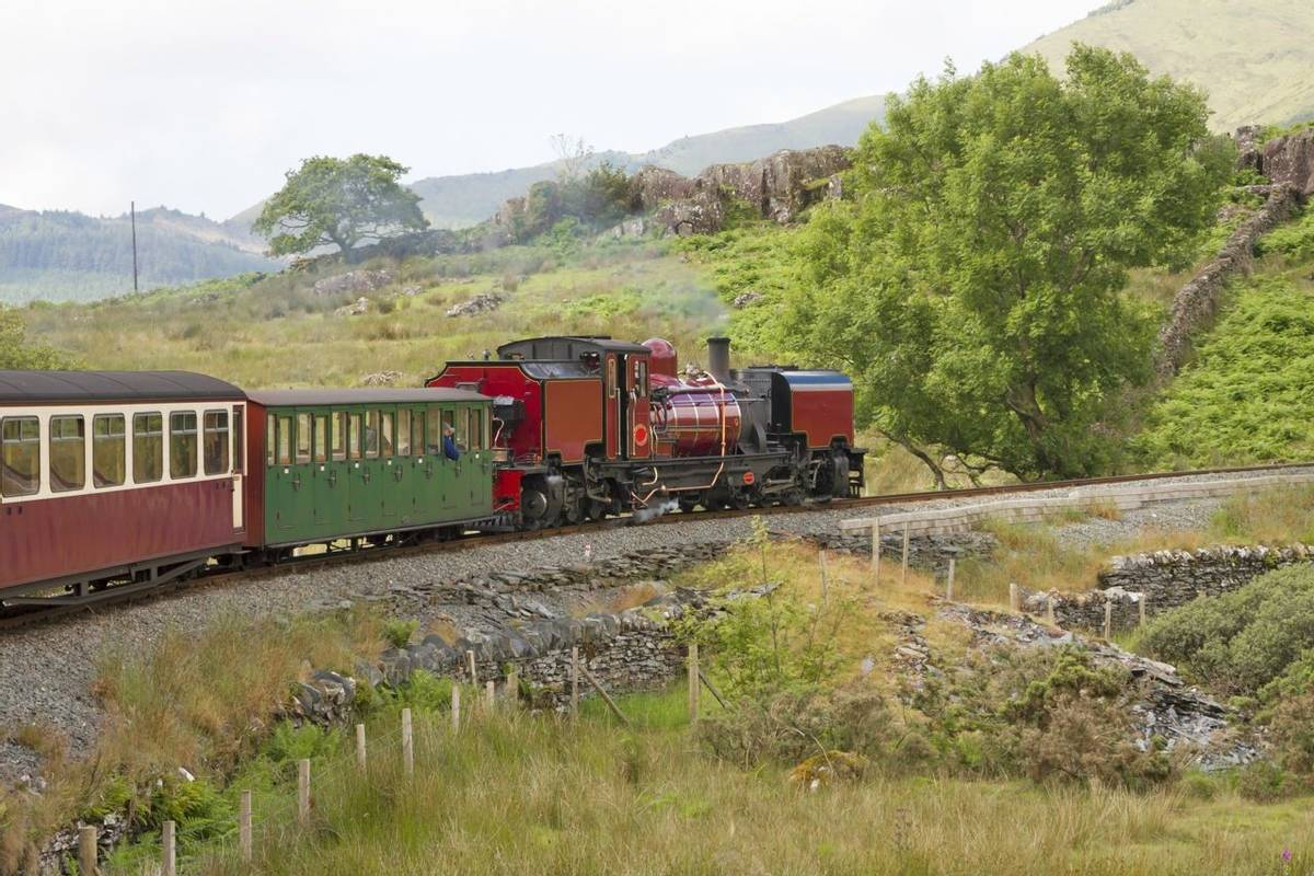 UK - Wales - Red steam locomotive (class garratt) pulls the old heritage train through Wales wilderness on Welsh Highland Ra…