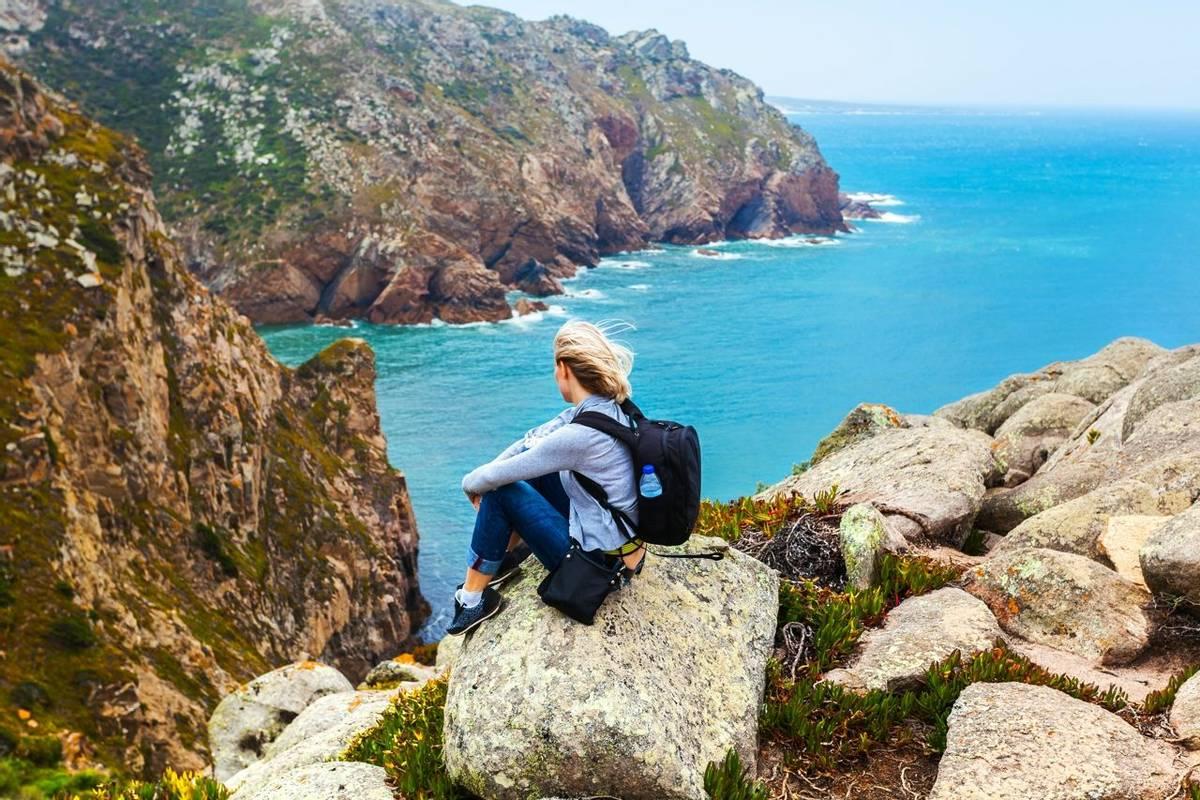 Female tourist sitting on Cape Roca, Sintra, Portugal