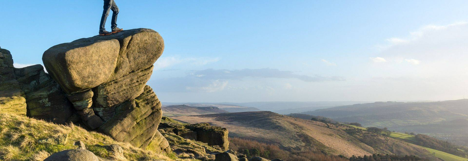 Young male hiker stood on rocky outcrop, Stanage Edge, Peak District.