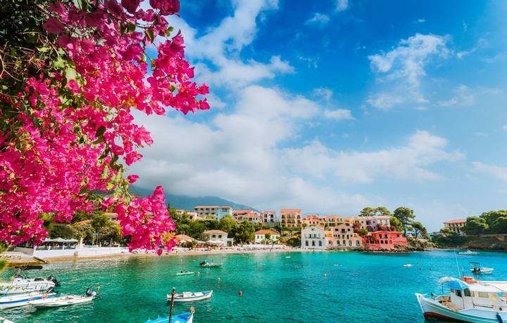 Beautiful Assos village scenery framed with branch of magenta blossom fuchsia flower. Summer vacation concept.