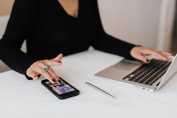 woman using phone and laptop at the same time