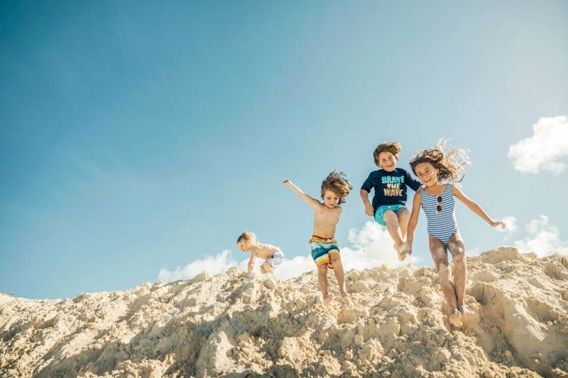 Children playing on sand dunes together