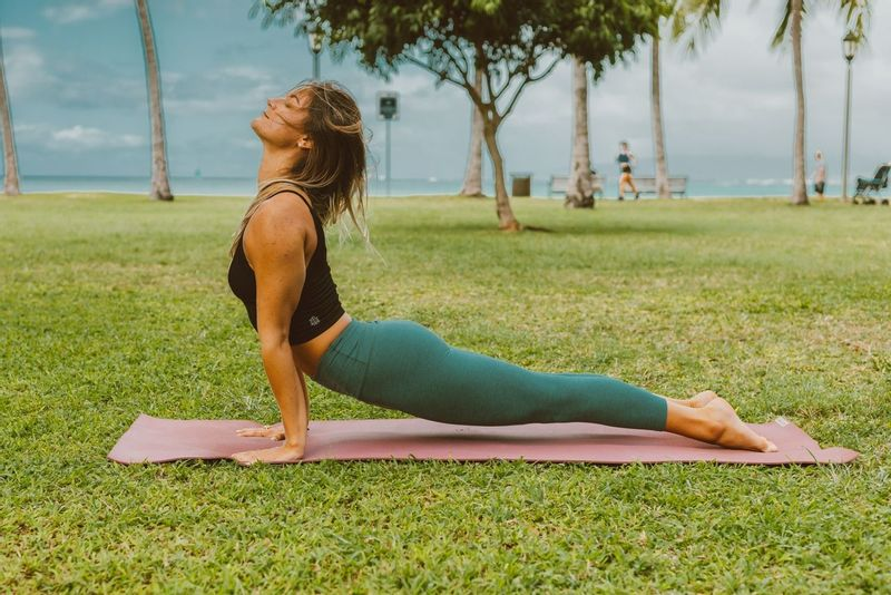 Woman practicing yoga on holiday on the grass with the sea in the background