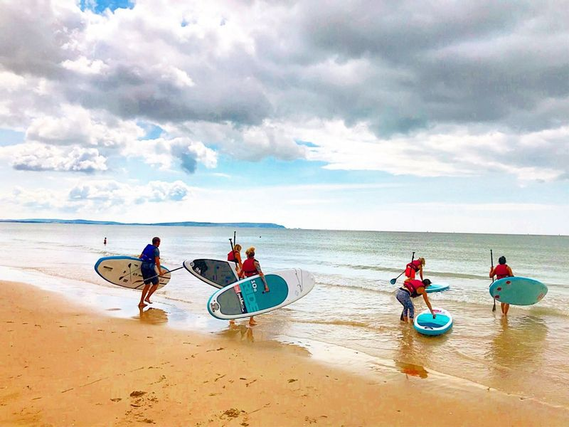 Groupe de personnes portant leurs paddleboards dans l'océan