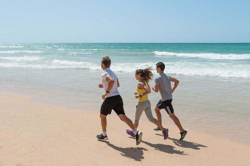 Group of people running on the beach
